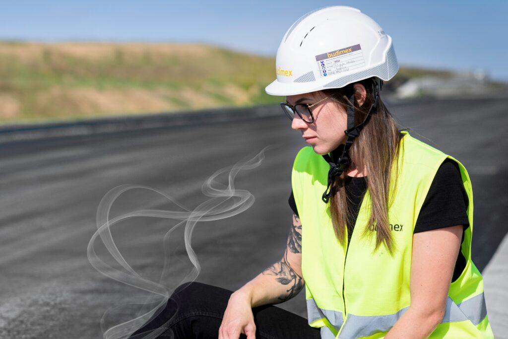 Bodymix and Lotus Asphalt working on scented asphalt - Woman sitting on an asphalt road.